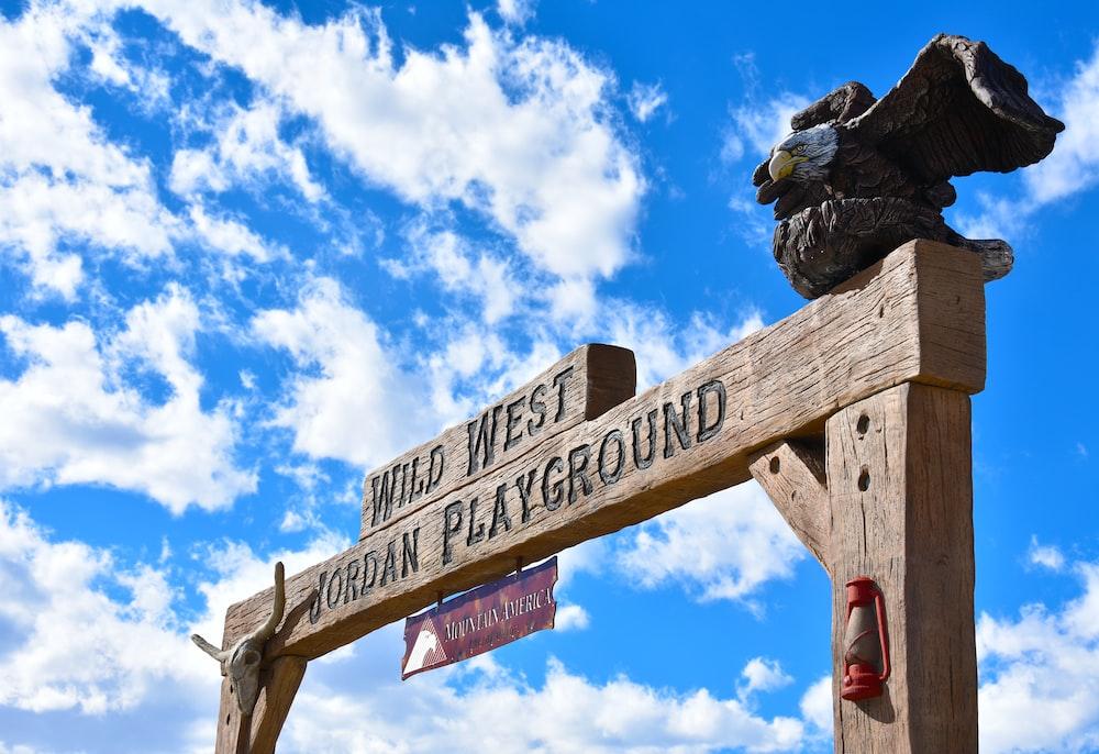 brown wooden signage under blue sky during daytime