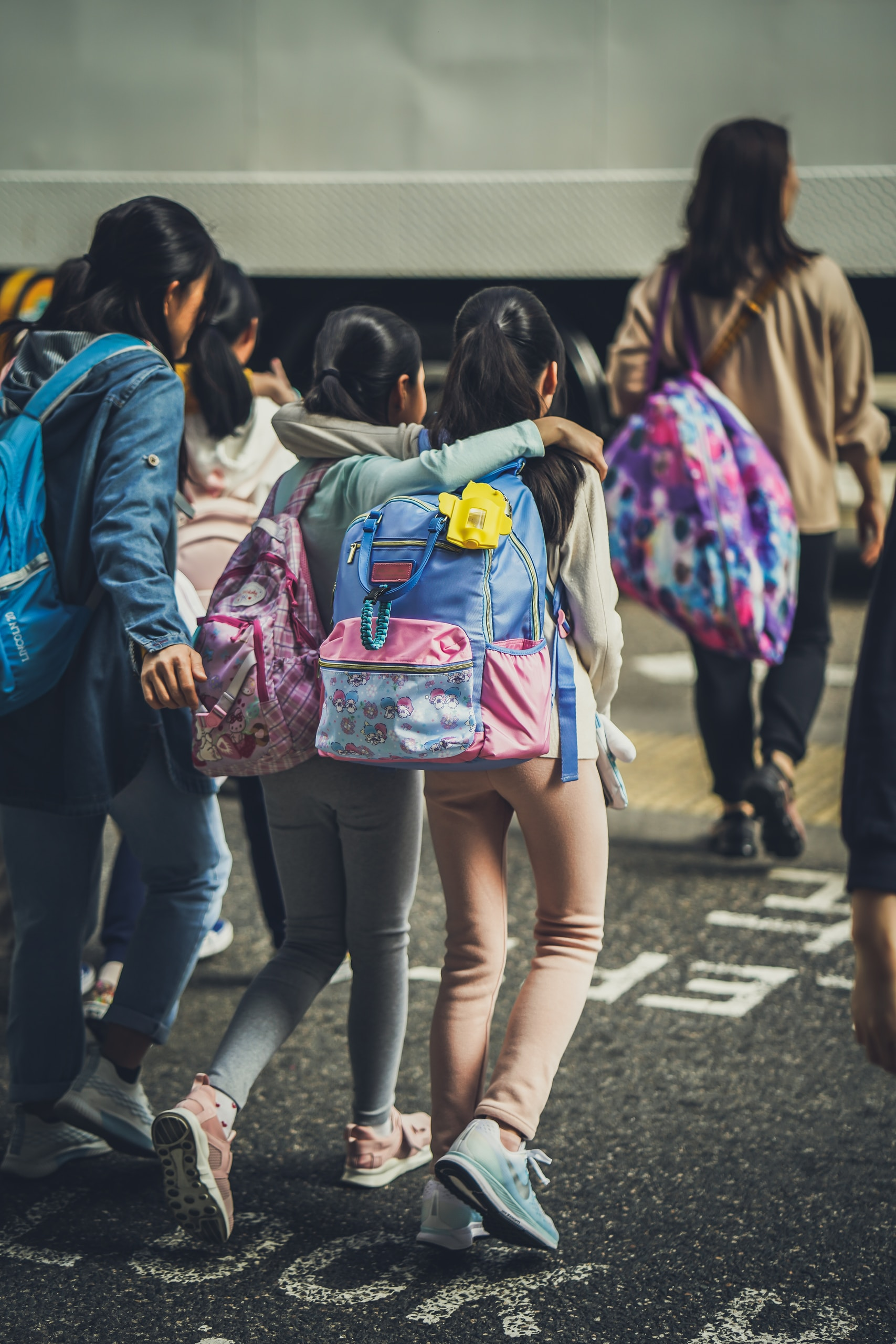 woman in blue jacket carrying pink backpack