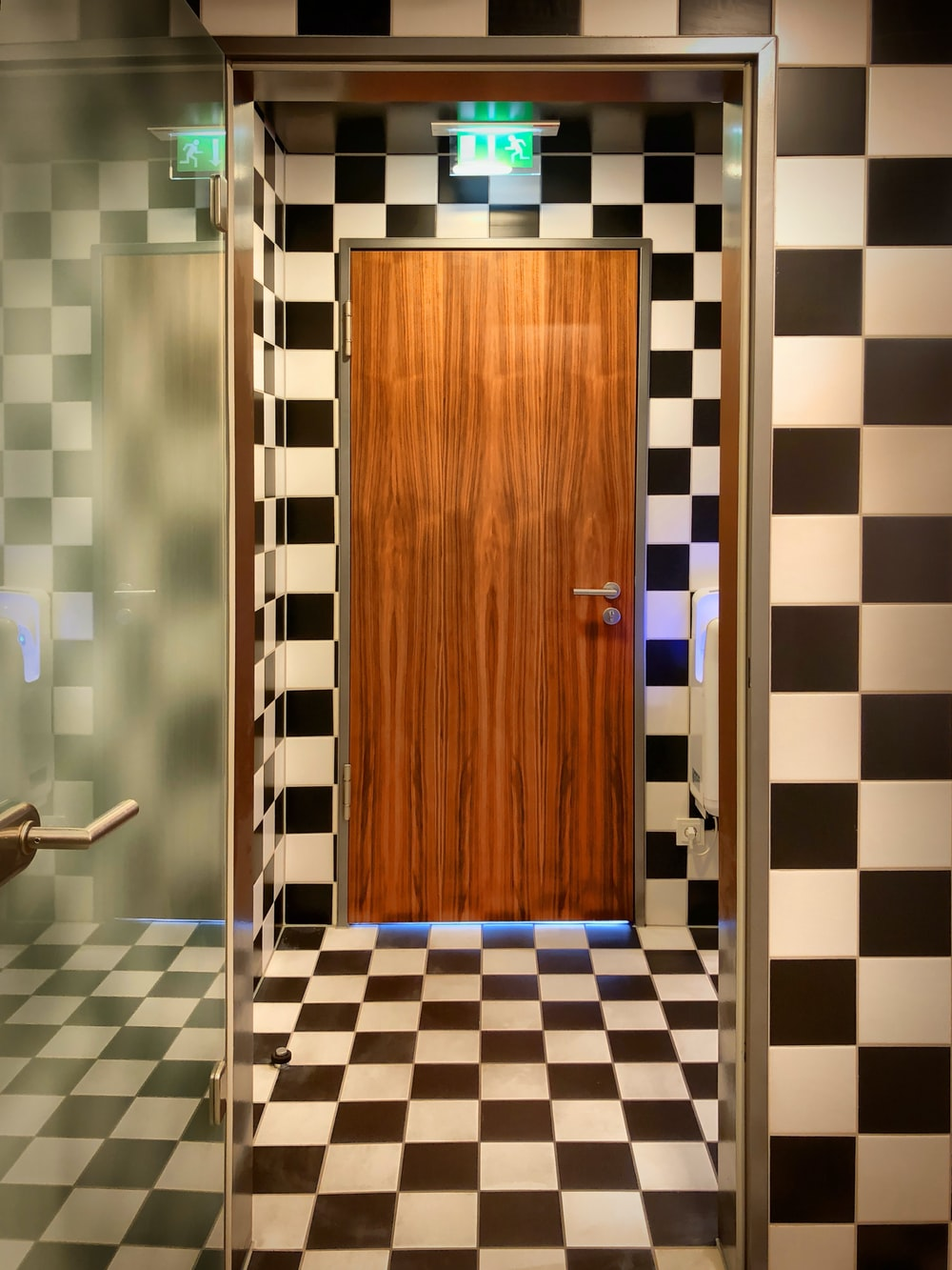 brown wooden door on blue and white checkered floor tiles