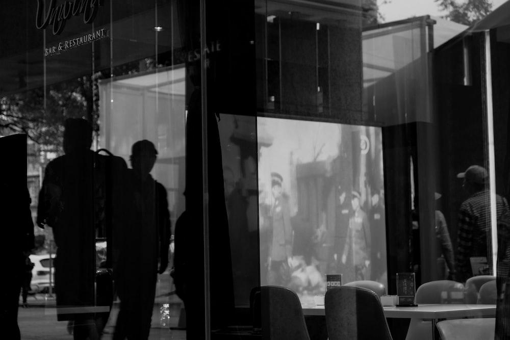 man in black suit standing near glass window