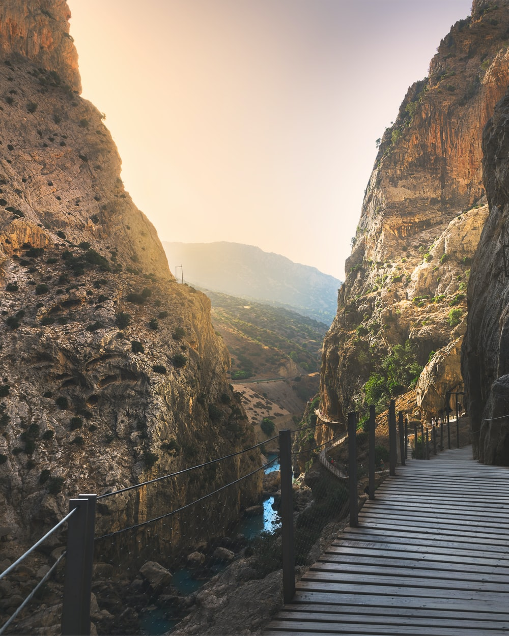 brown wooden bridge between brown rocky mountains during daytime
