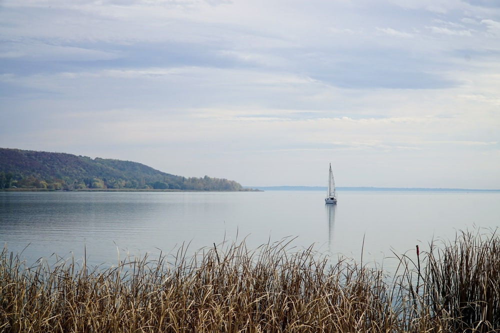 white sailboat on sea under white clouds during daytime