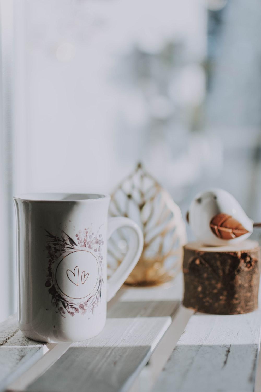 white ceramic mug beside white ceramic mug on brown wooden table