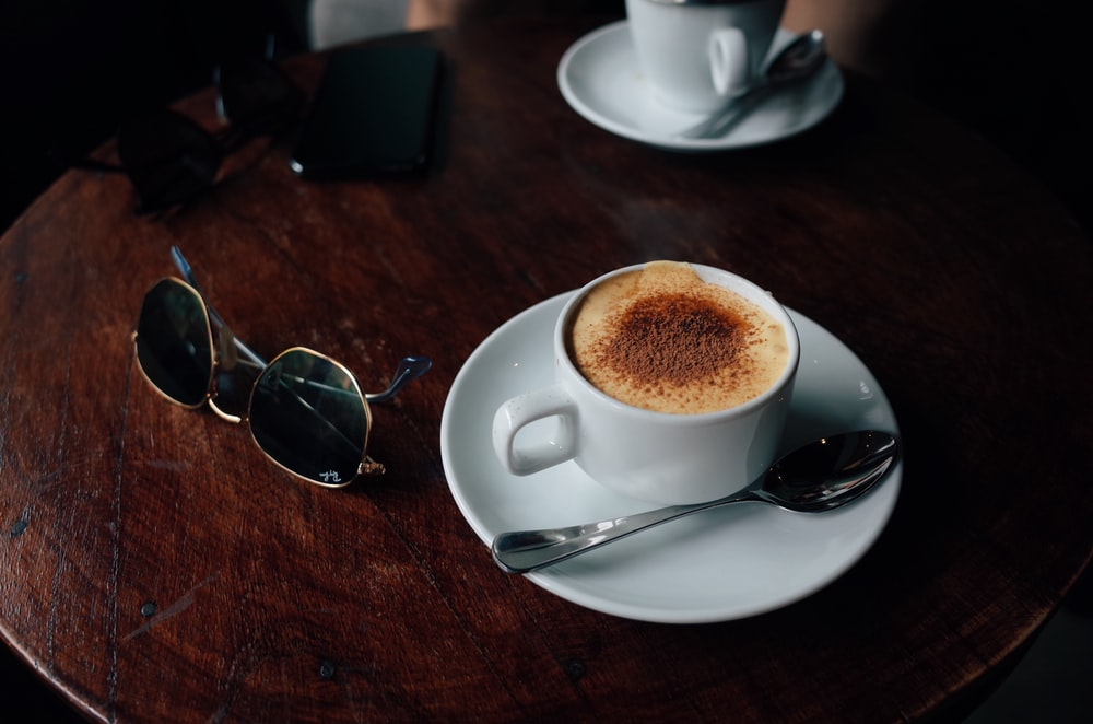 white ceramic cup with saucer beside silver framed aviator sunglasses