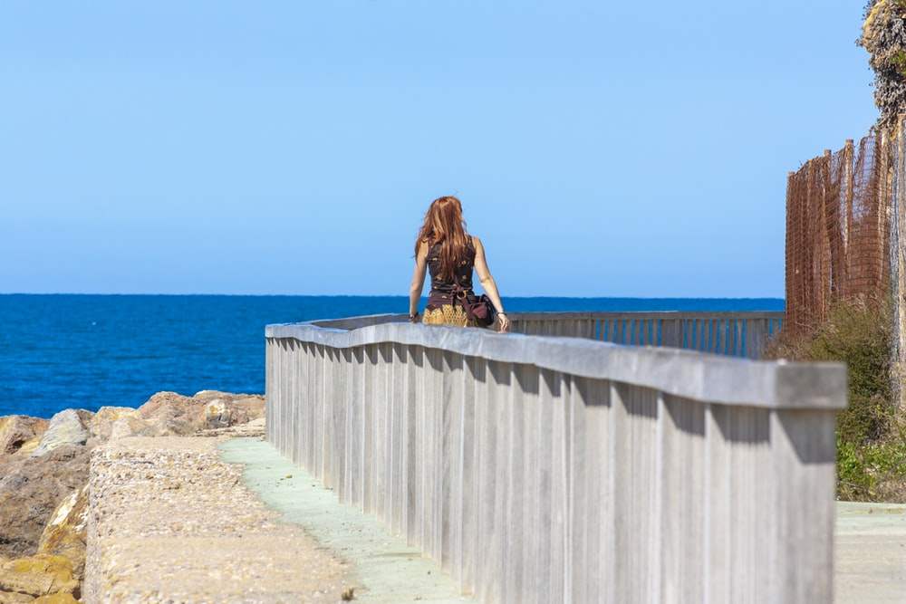 woman in brown jacket sitting on concrete fence near sea during daytime