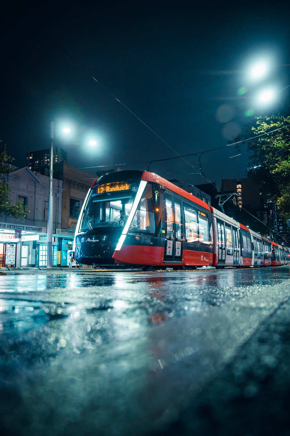 red and white tram on road during night time