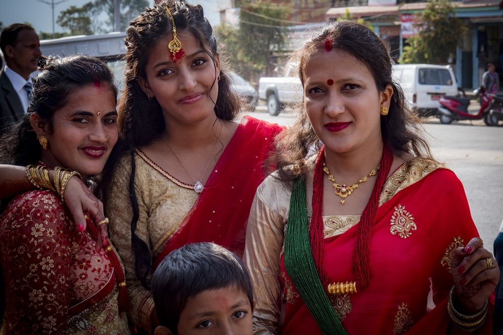 woman in red and green sari beside girl in green and brown dress
