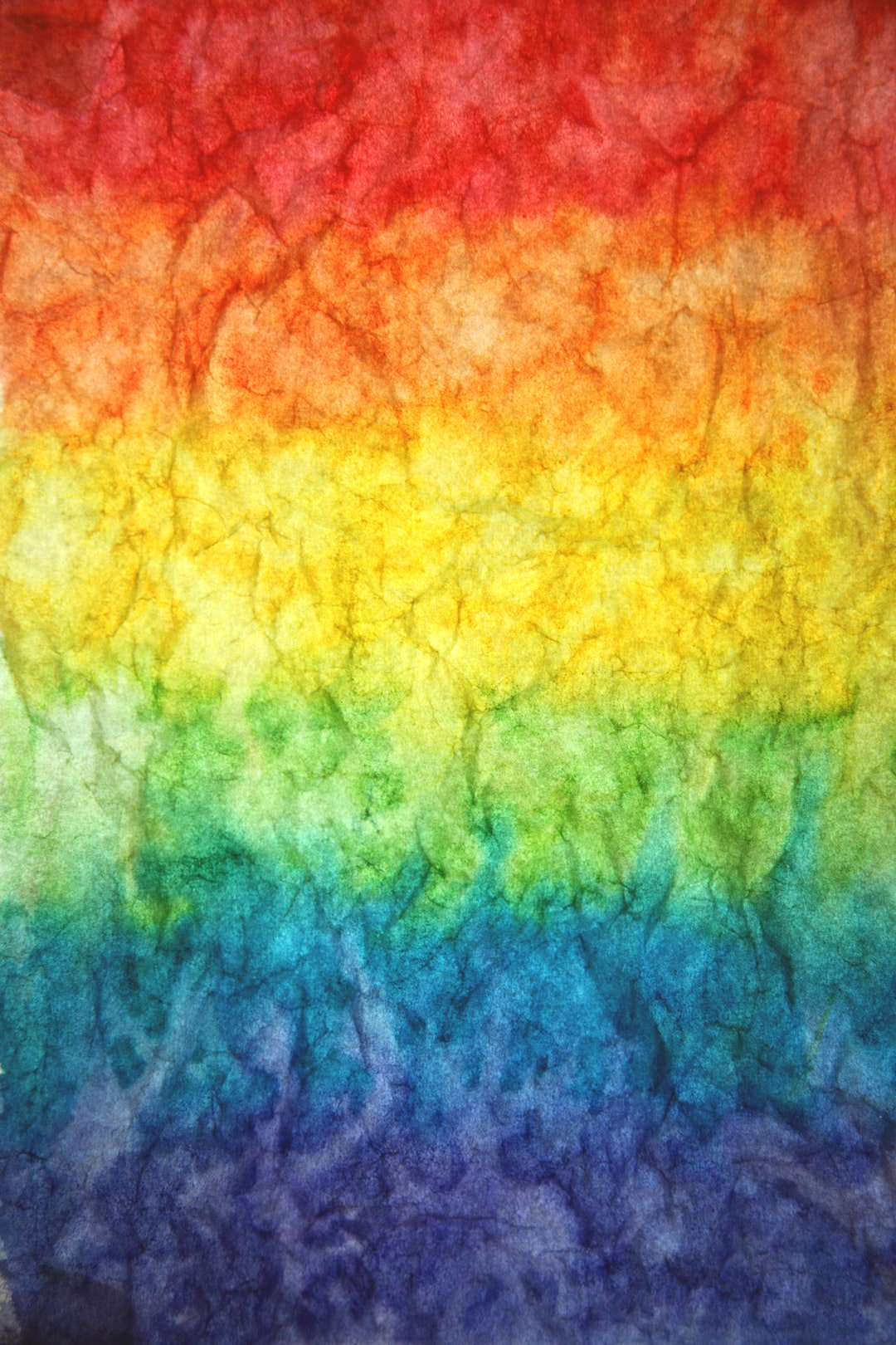 Textured paper watercolor paint rainbow background.