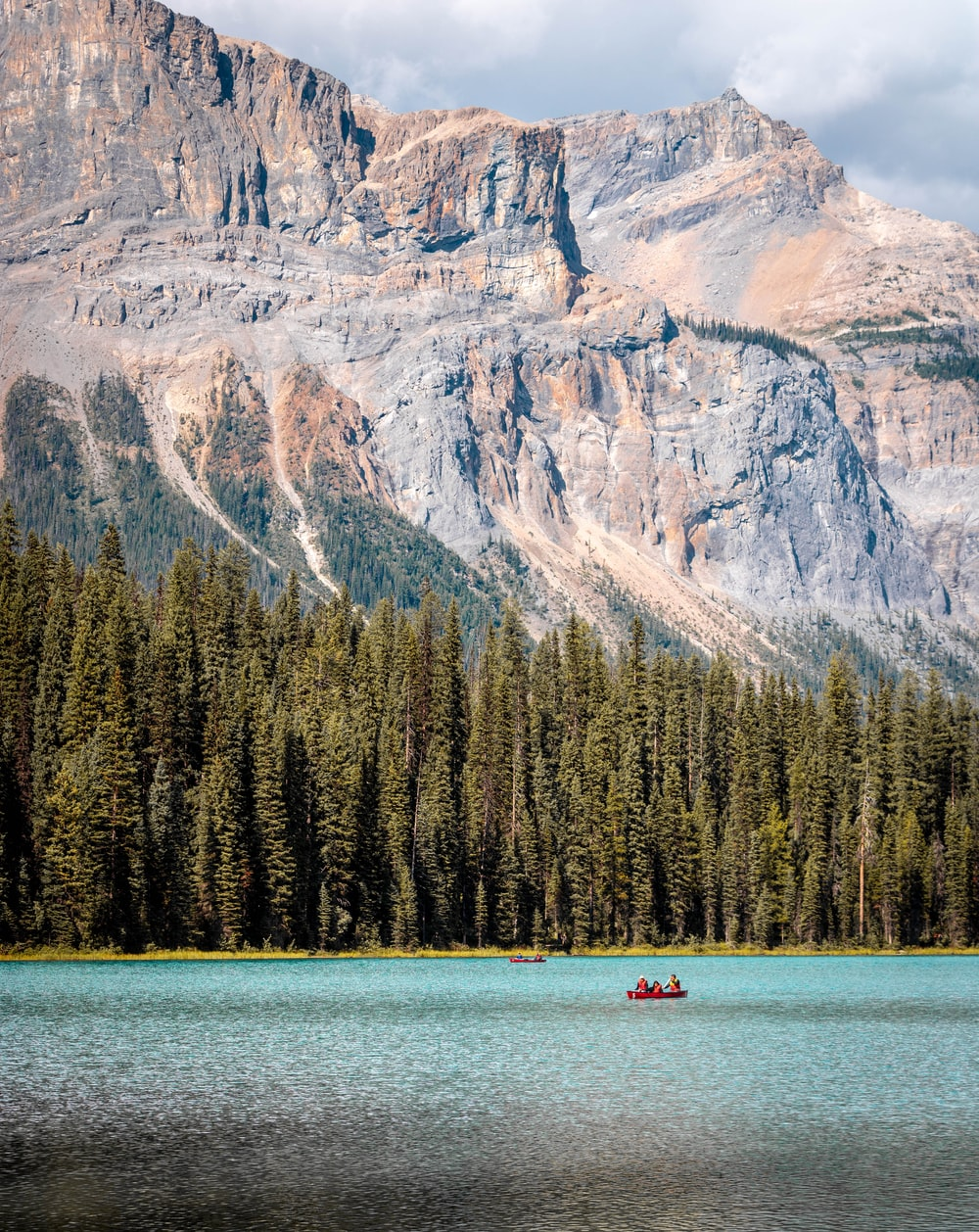 person riding on boat on lake near mountain during daytime