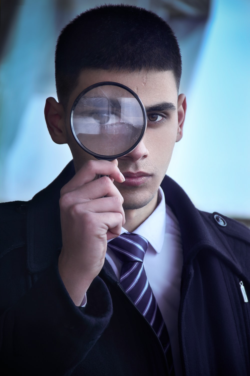 man in black suit holding magnifying glass