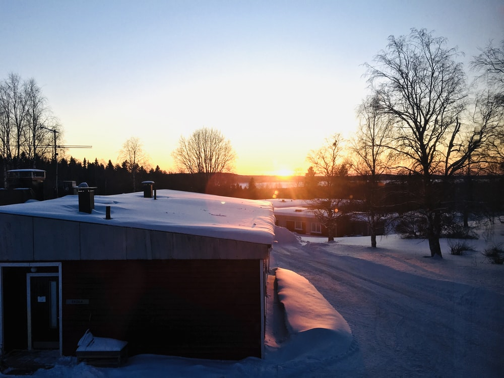 brown wooden house covered with snow during sunset