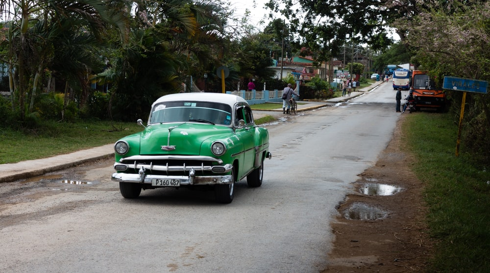 green classic car on road during daytime