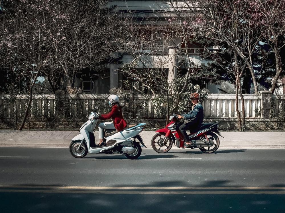2 person riding on motorcycle on road during daytime