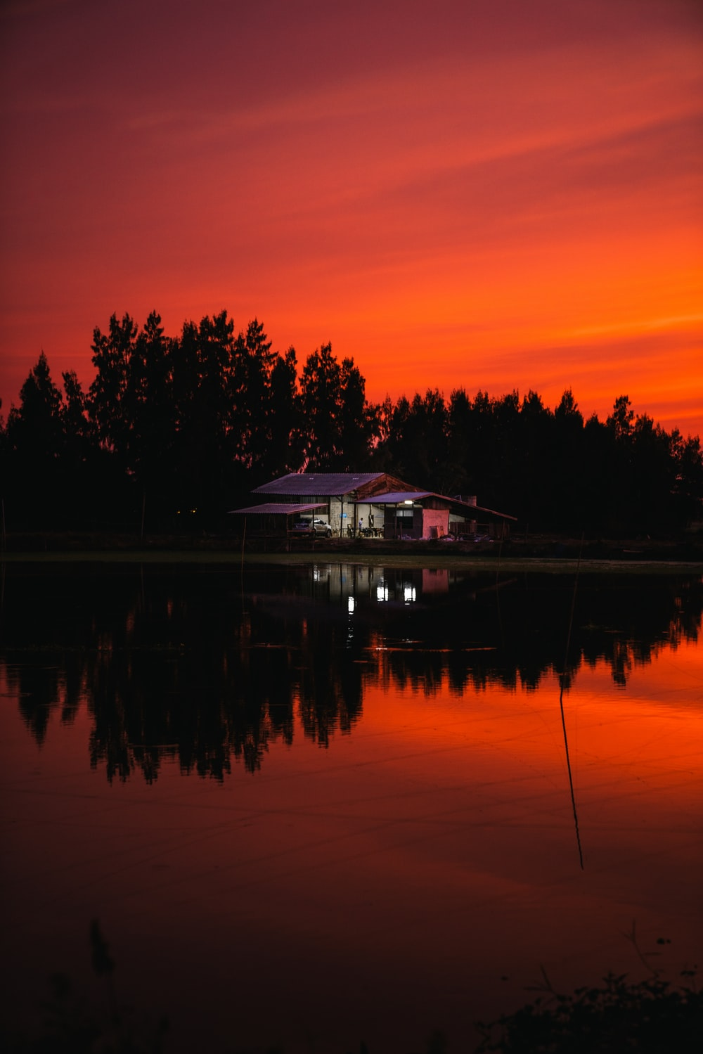 silhouette of house near body of water during sunset