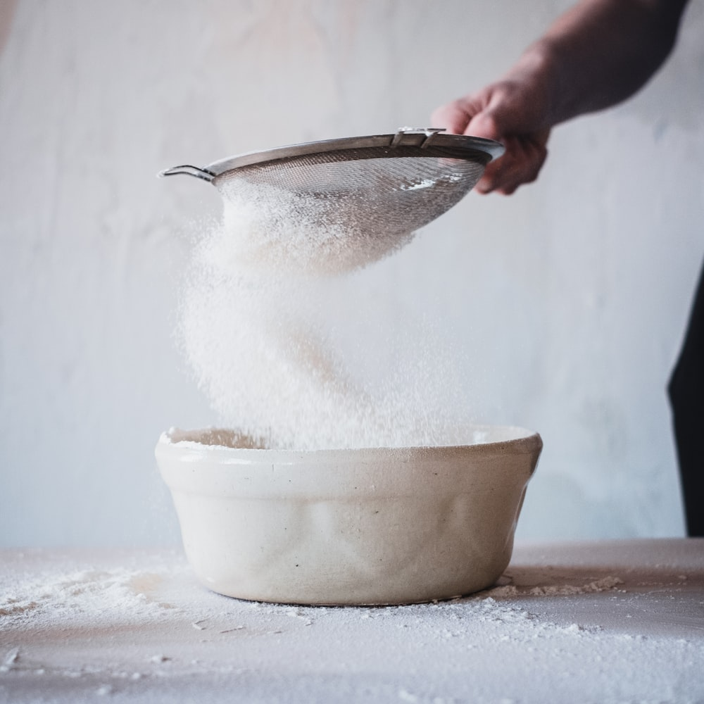 person pouring water on white ceramic bowl