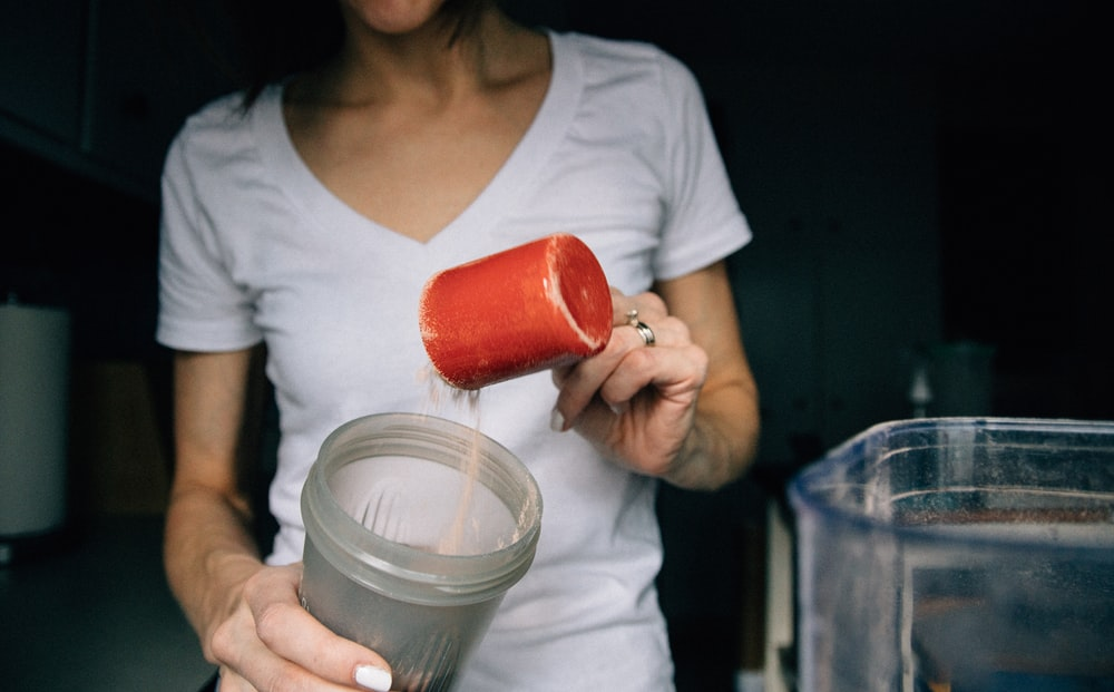 woman in white crew neck t-shirt holding red plastic cup