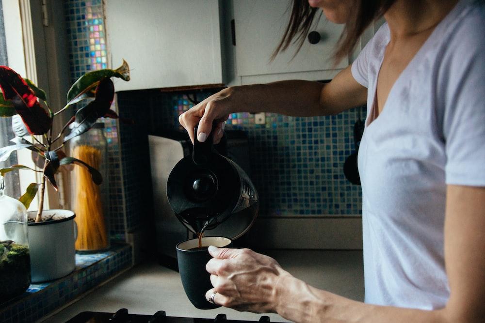 woman in white t-shirt holding black ceramic mug