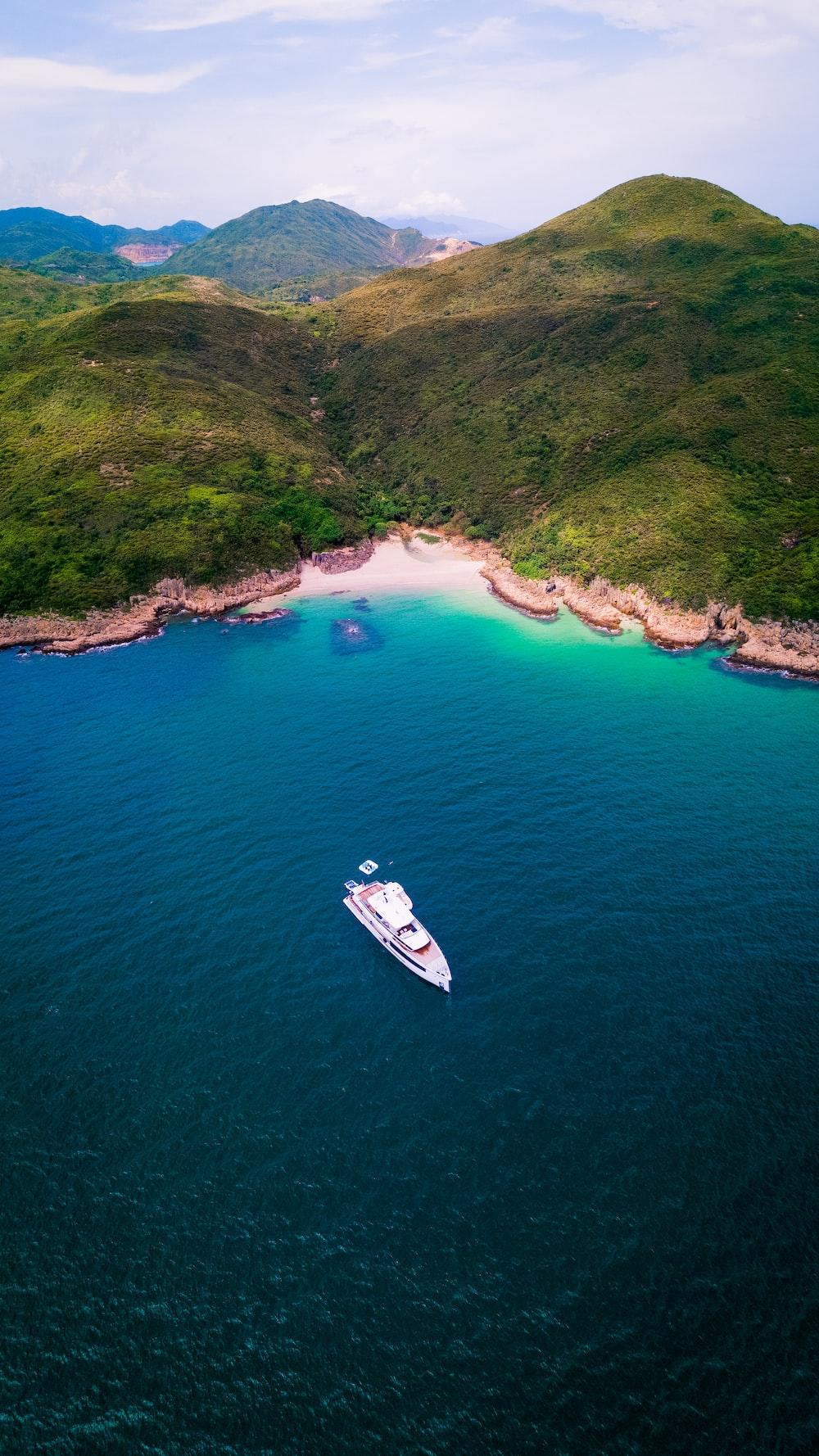 white boat on sea near green mountain during daytime