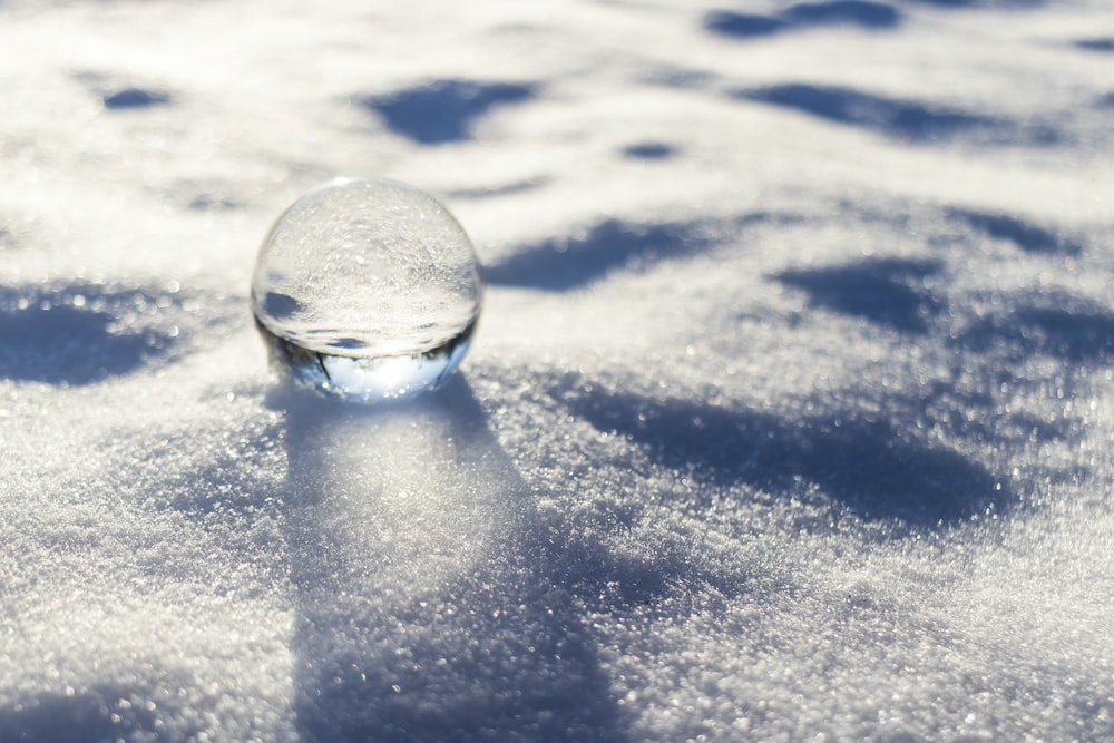 clear glass ball on white snow