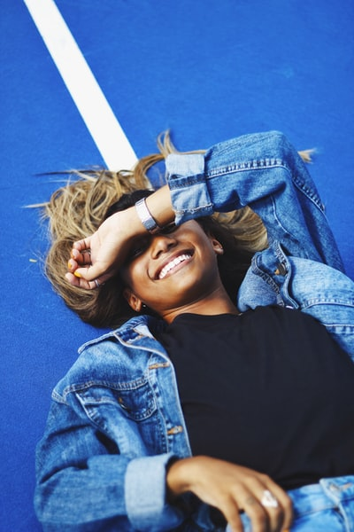 woman in black shirt and blue denim jacket smiling