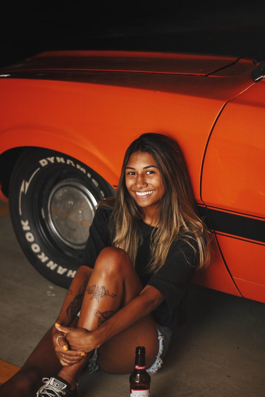 woman in black long sleeve shirt sitting on orange car