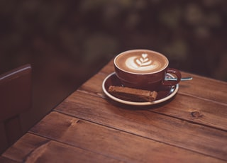 cappuccino in brown ceramic cup on brown wooden table
