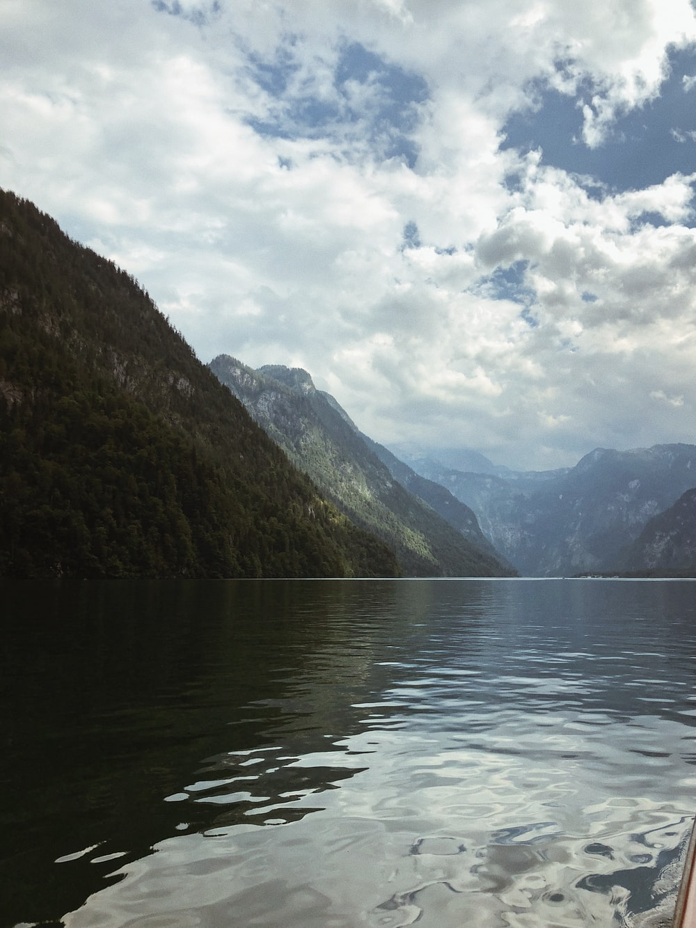 green mountains beside body of water under cloudy sky during daytime