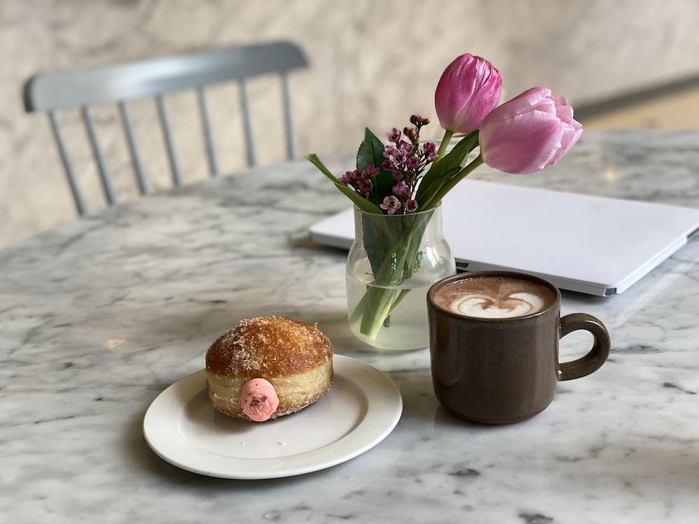 brown bread on white ceramic plate beside black ceramic mug
