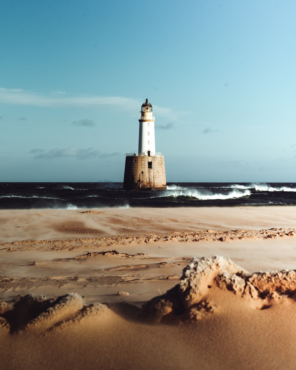 white and black lighthouse on brown sand near body of water during daytime