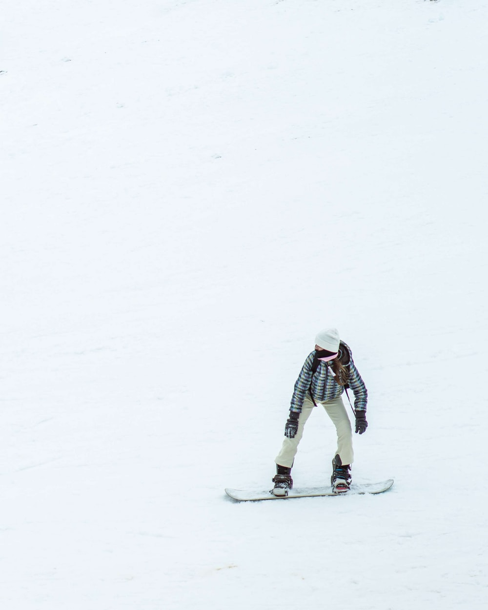person in white jacket and black pants riding snow ski