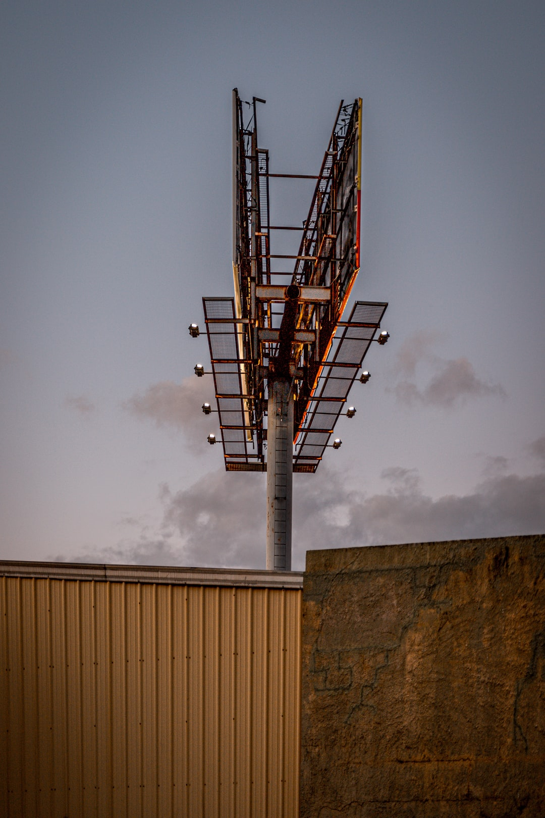 Looking up at an outdoor board and warehouse at sunset with empty sky in background.