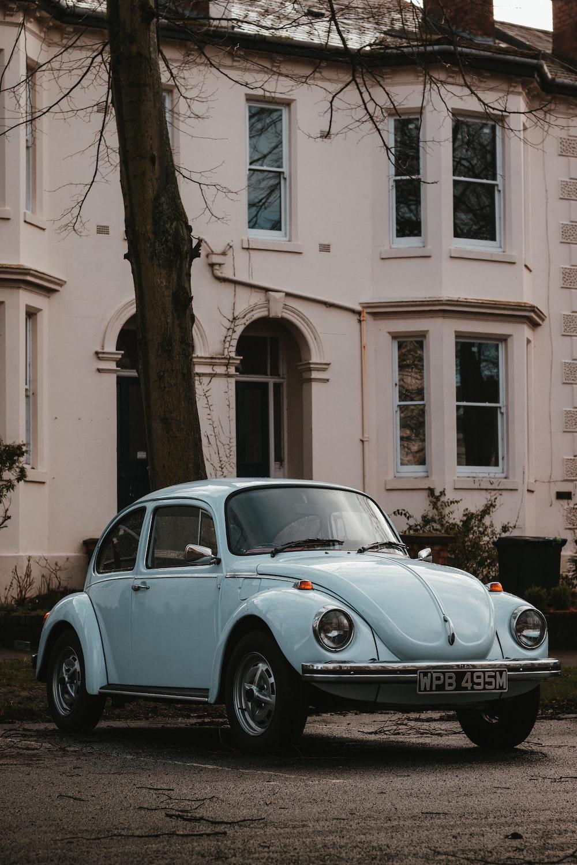 blue volkswagen beetle parked beside brown concrete building during daytime