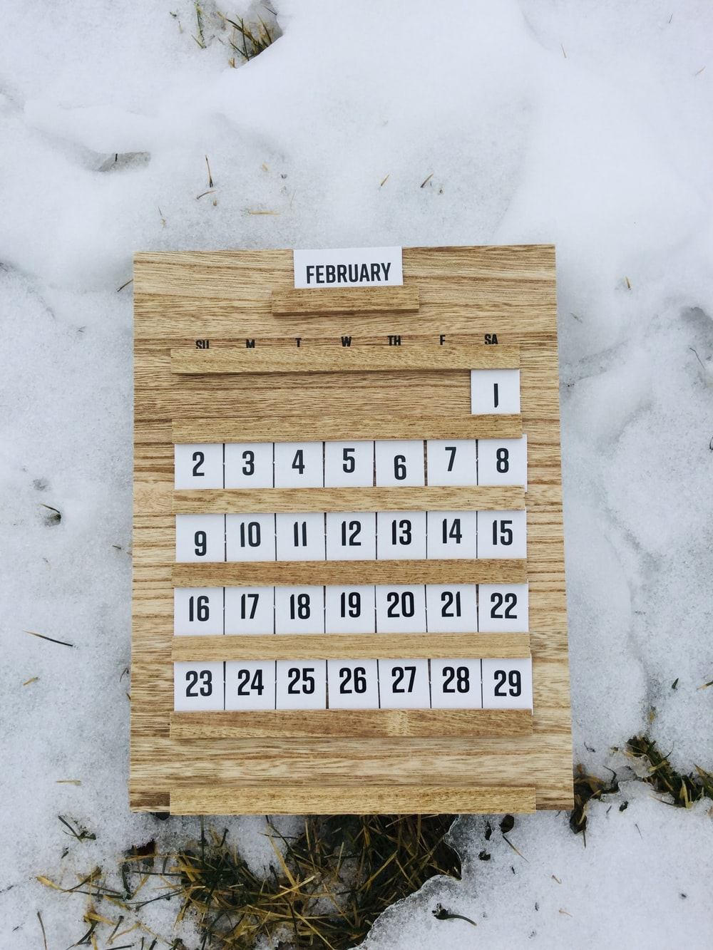 brown wooden board with white and black texts