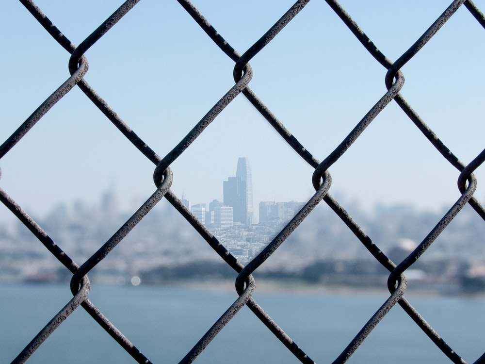 gray chain link fence across city buildings during daytime
