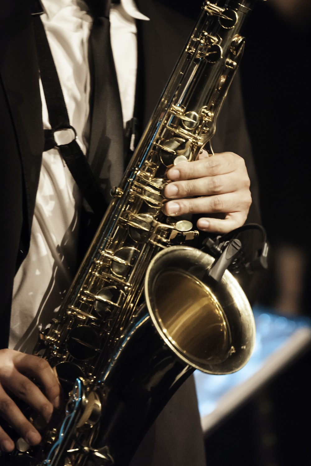 person in white dress shirt holding saxophone