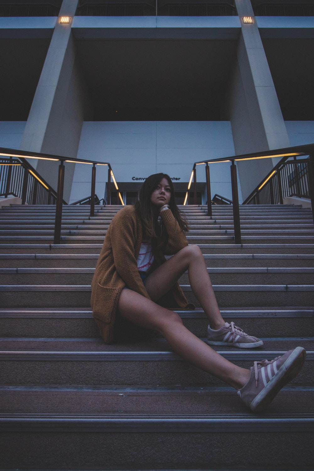 woman in brown coat sitting on stairs
