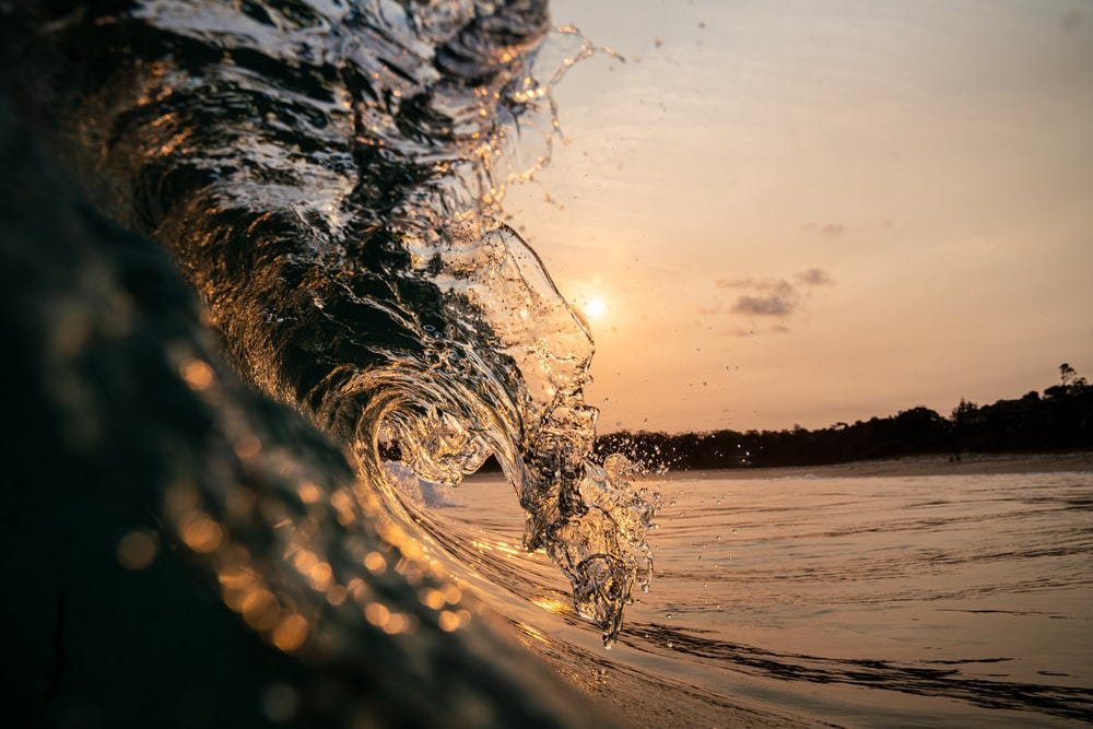 water splash on body of water during sunset