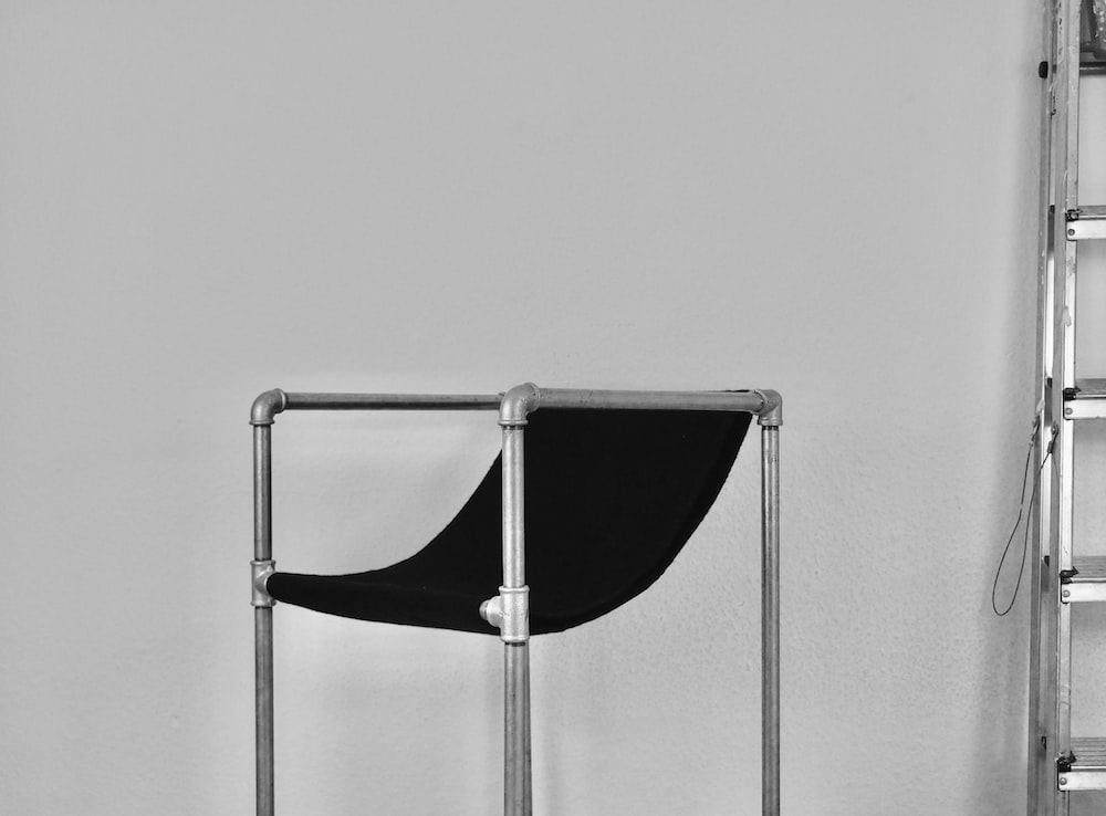 black and silver chair beside white wall
