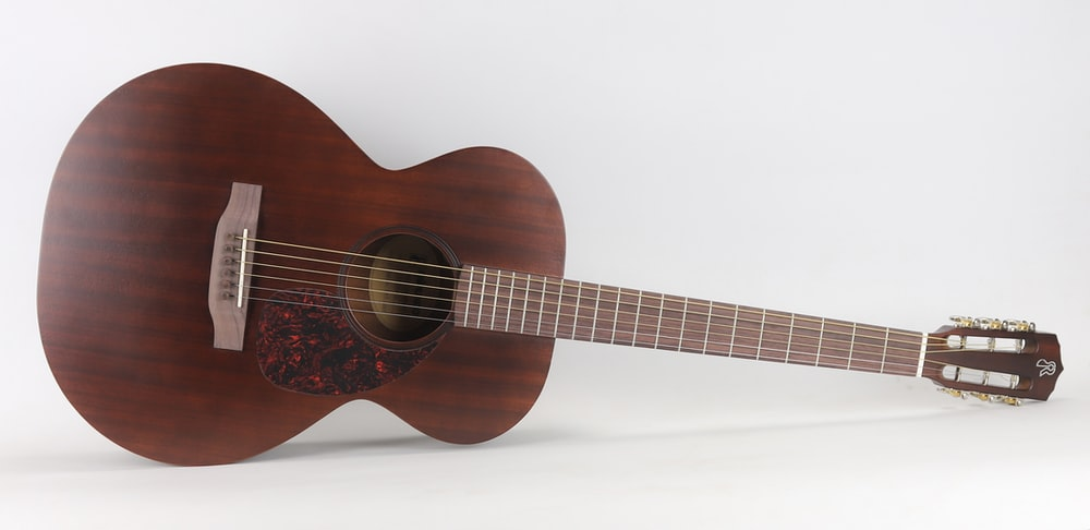 brown acoustic guitar on white background