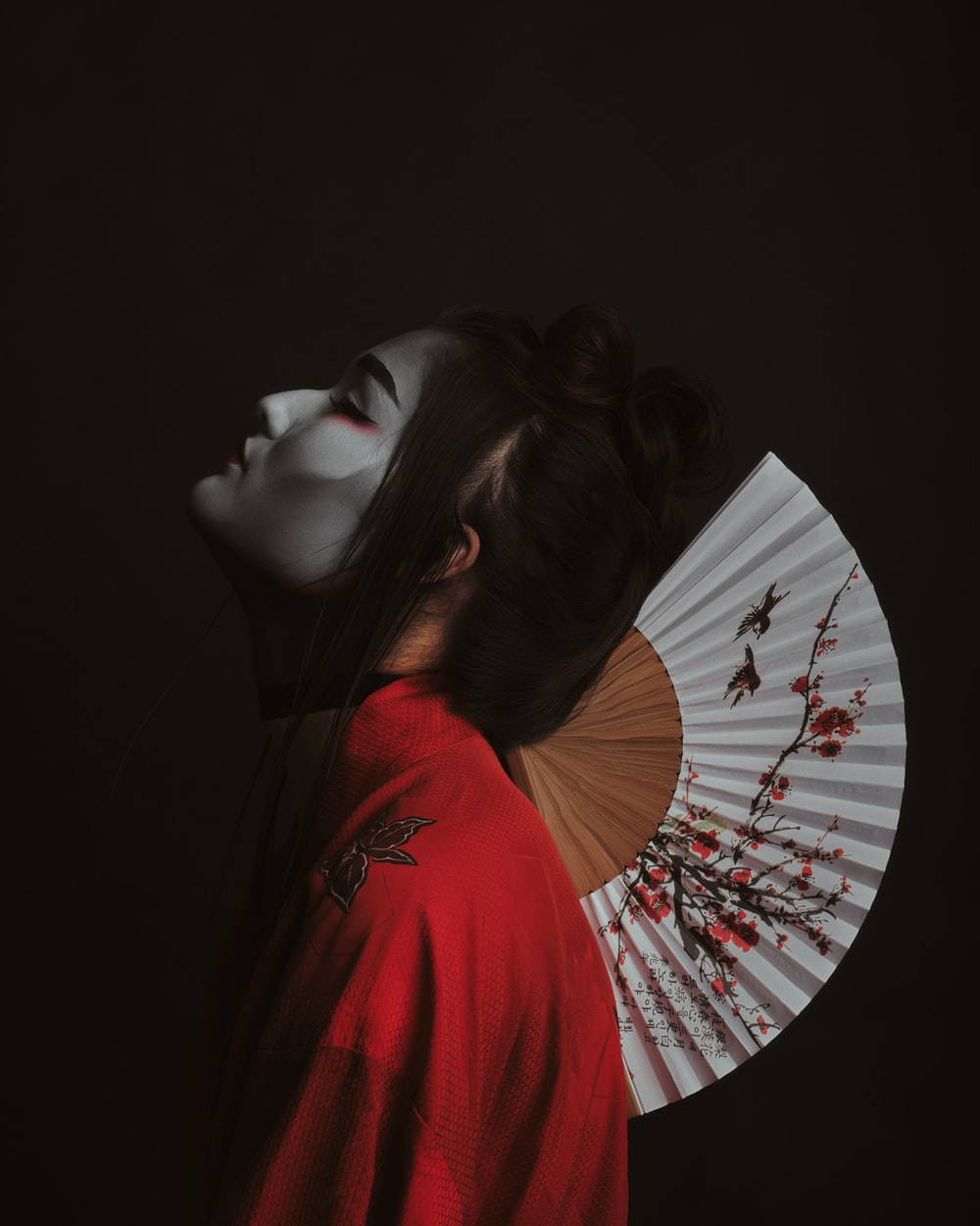 woman in red shirt covering her face with white and black floral hand fan