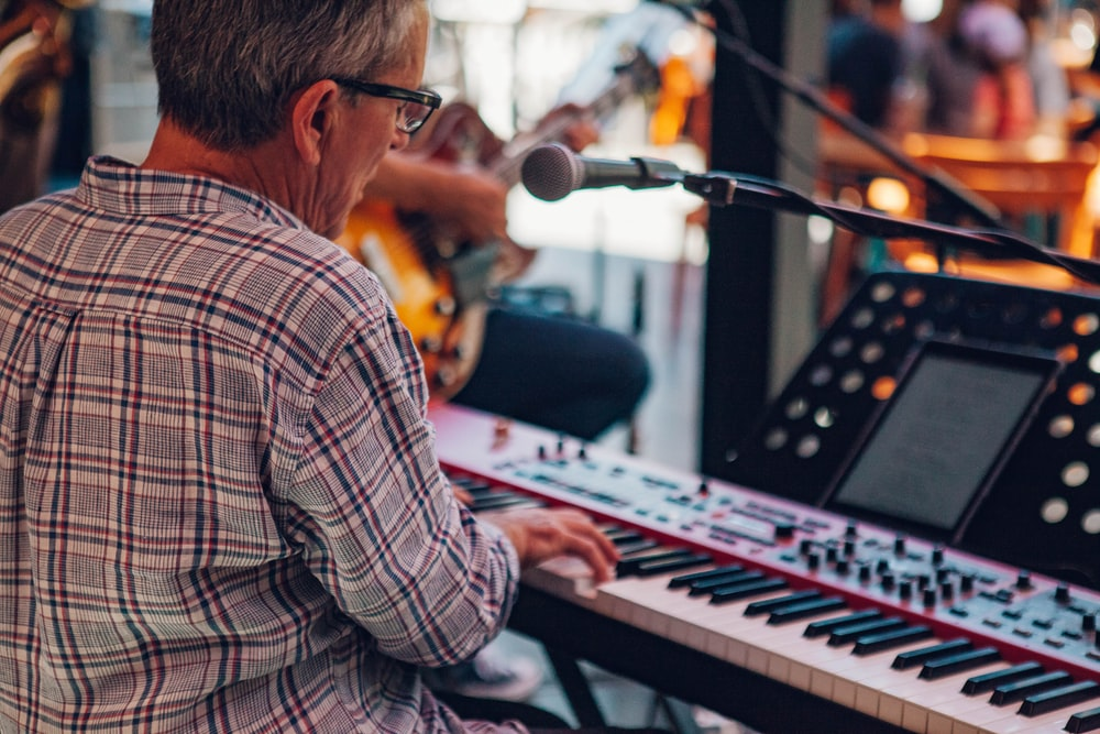 man in white and brown plaid dress shirt playing electric keyboard