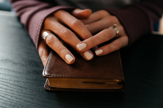 Woman's hands folded in prayer on a Bible