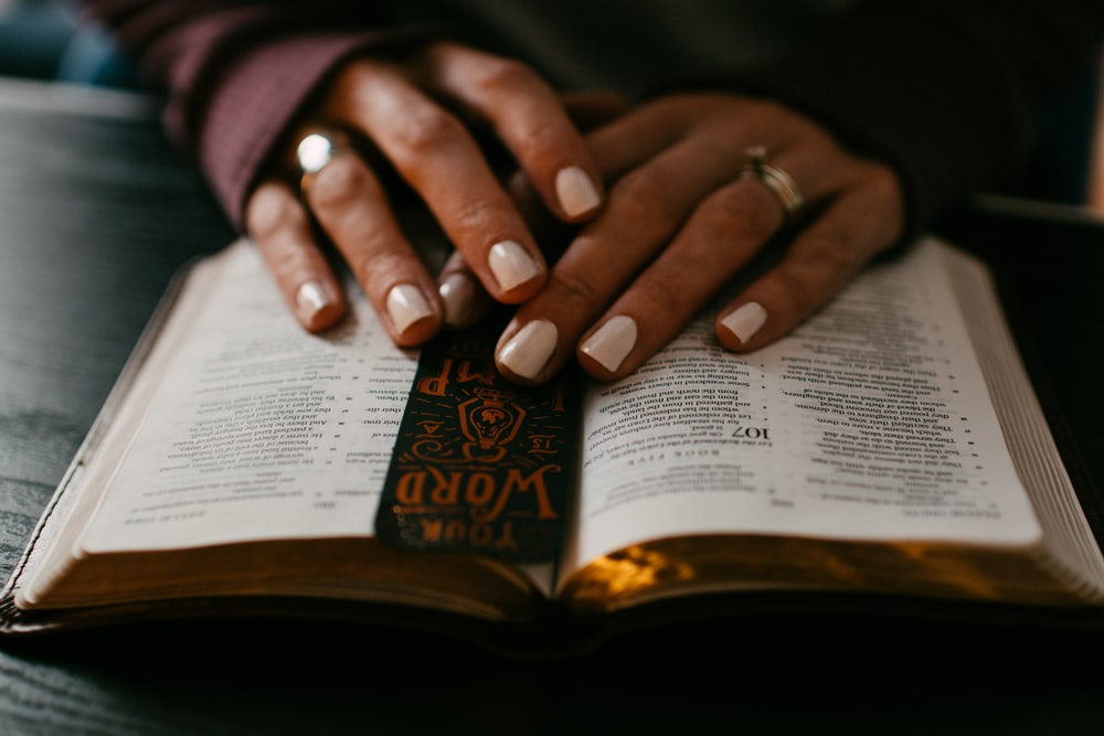 person wearing silver ring on ring finger on book page