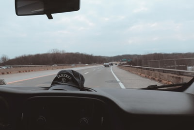 person in black and white cap driving car on road during daytime yankees zoom background