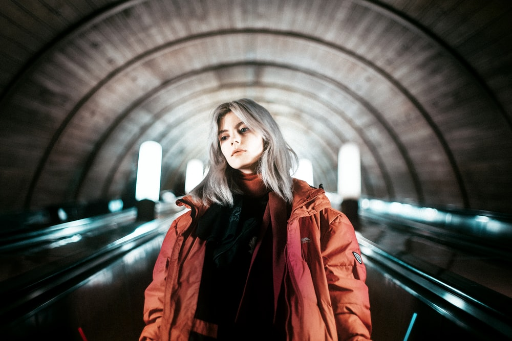 woman in red coat standing on tunnel