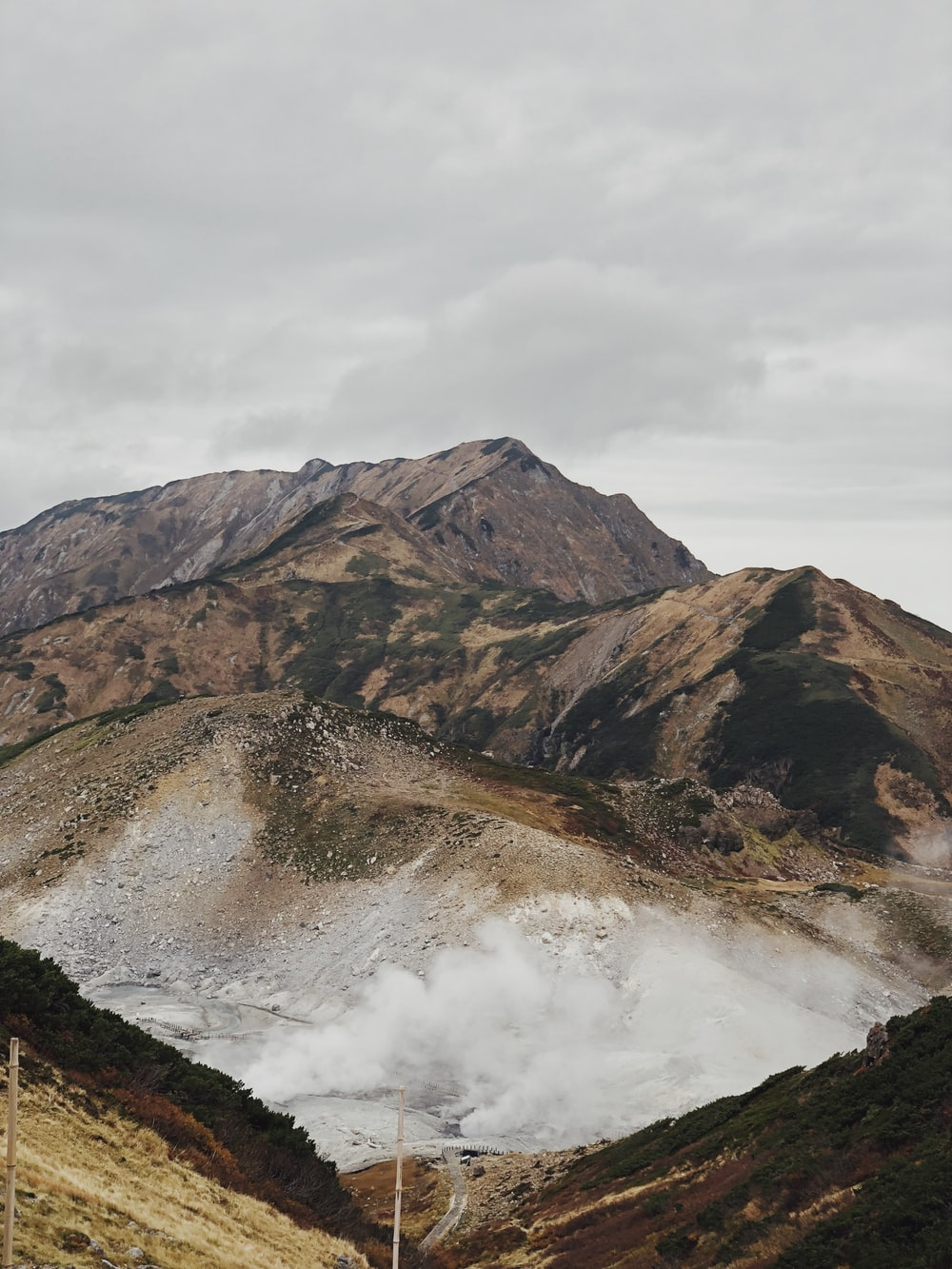 brown and green mountains under white clouds during daytime