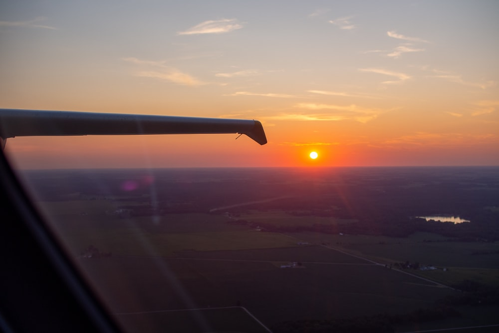 airplane wing over the city during sunset