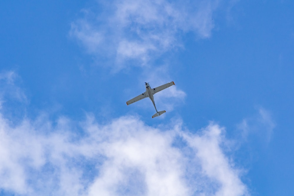 white plane in mid air during daytime