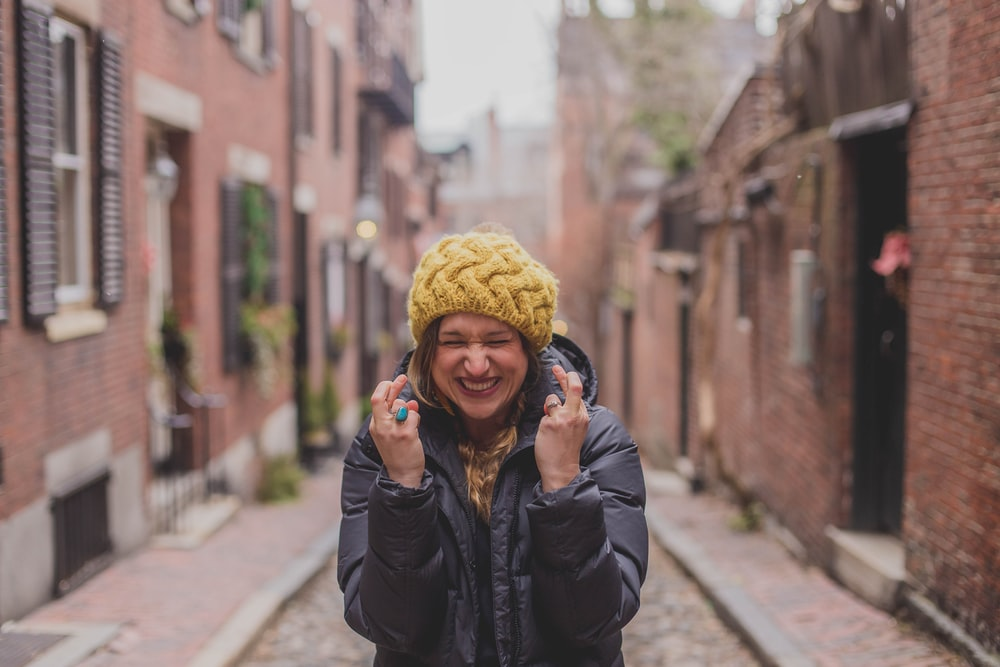 woman in black jacket and yellow knit cap standing on sidewalk during daytime