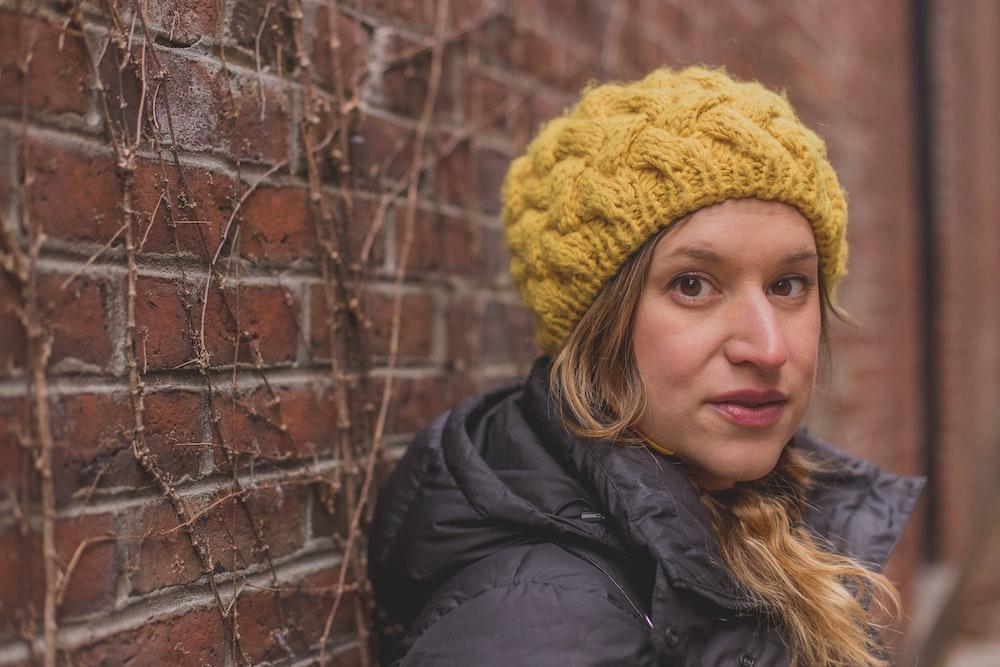 woman in black jacket wearing yellow knit cap